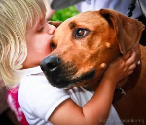 Kind drückt Hund an sich